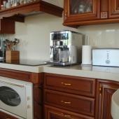 Каменная столешница отлично смотрится с деревянными фасадами кухни